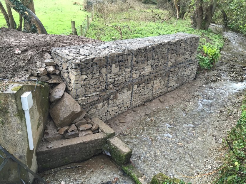Two layers of gabion baskets were installed and back filled, this was to divert the water from its natural course, to avoid potential flooding of a North Devon Factory, built by MJS Building Maintenance Ltd.