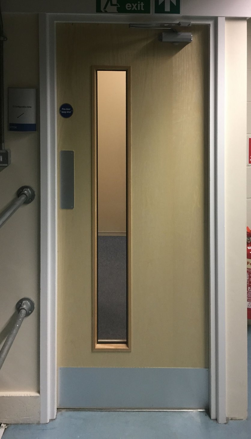 Old doors removed, installed replacement Ash doors with vision panels. New fire rated ironmongery fitted, correct signage, door closures and intumescent smoke seals for a North Devon Factory