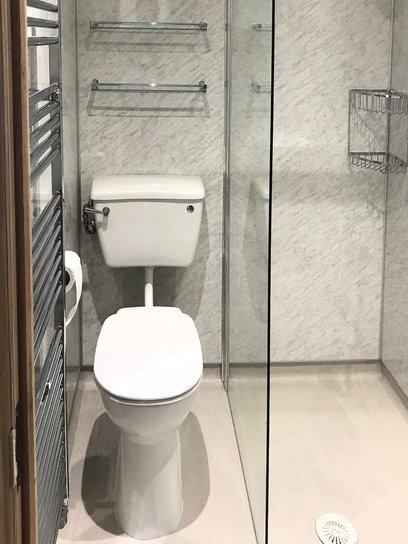 High level WC pan with low level cistern installed. High level glass shelves fitted with chrome retaining rail. Barnstaple North Devon