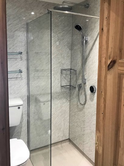 12mm thick toughened safety glass frameless wetroom shower screen with chrome basket shower fittings. Barnstaple North Devon