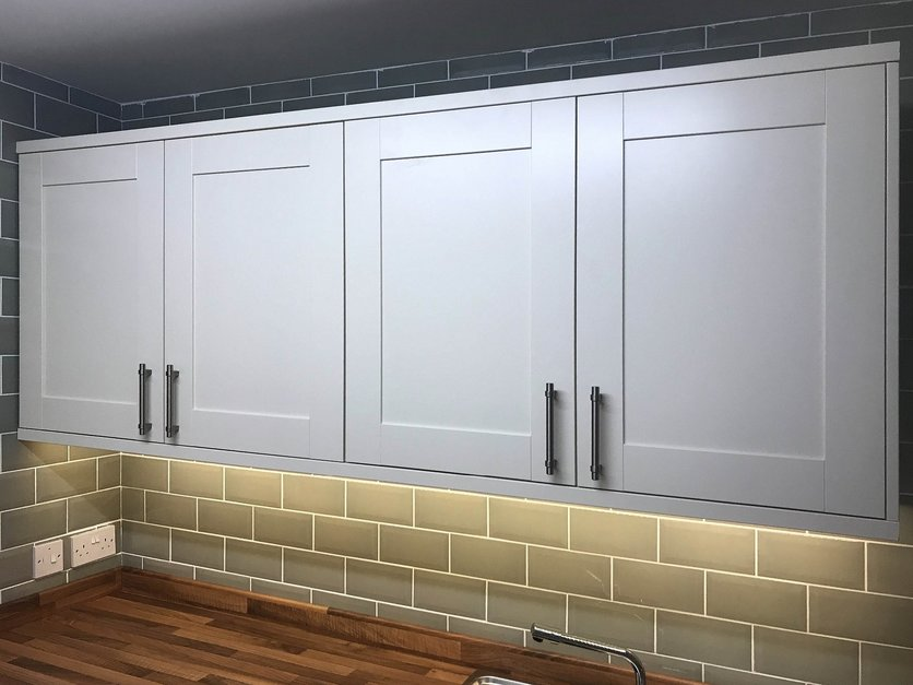 Bank of wall hung cabinet units with under pelmet led lighting part of kitchen installation. Barnstaple Devon